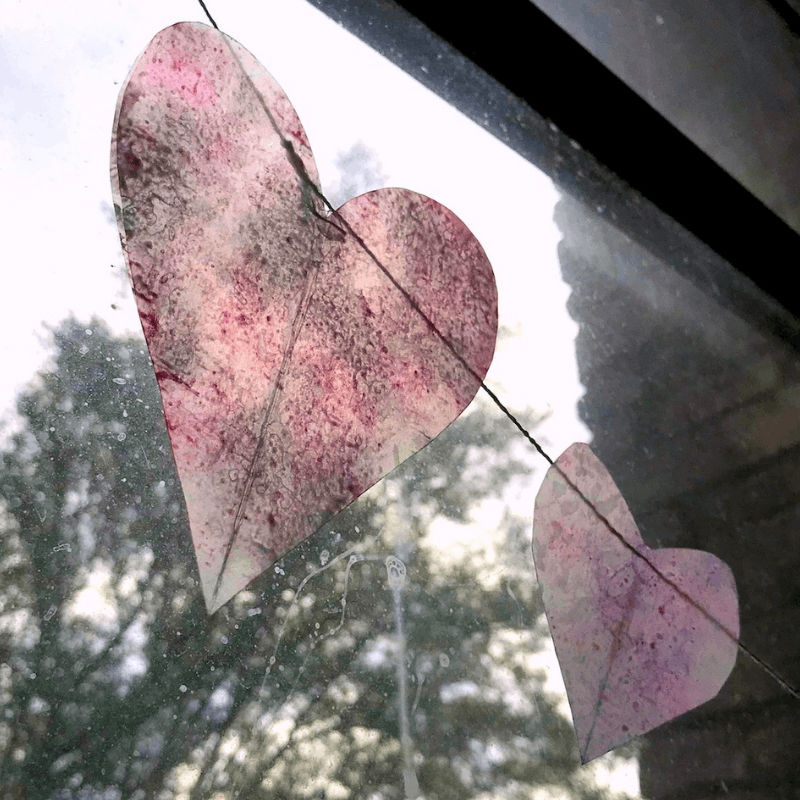 Make a pretty Valentines Heart Garland to hang in your window this year. It's a great way to add a splash of color! | WildflowersandWanderlust.com