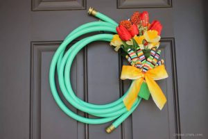 A water hose makes the perfect base for a spring wreath for your front door via Create Craft Love and showcased on WildflowersAndWanderlust.com