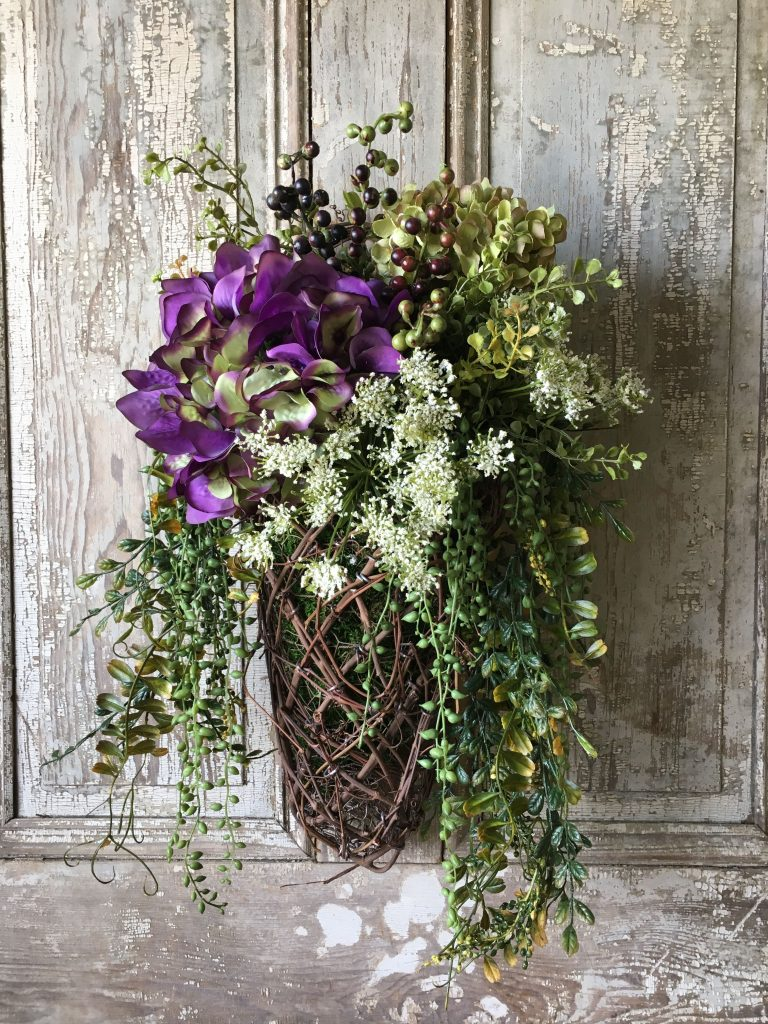 A basket to hang on your front door is a good alternative to a round wreath for spring | WildflowersAndWanderlust.com