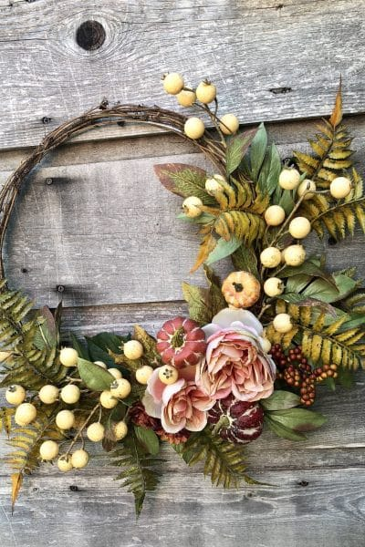 A fall wreath featuring roses and berries WildflowersAndWanderlust.com