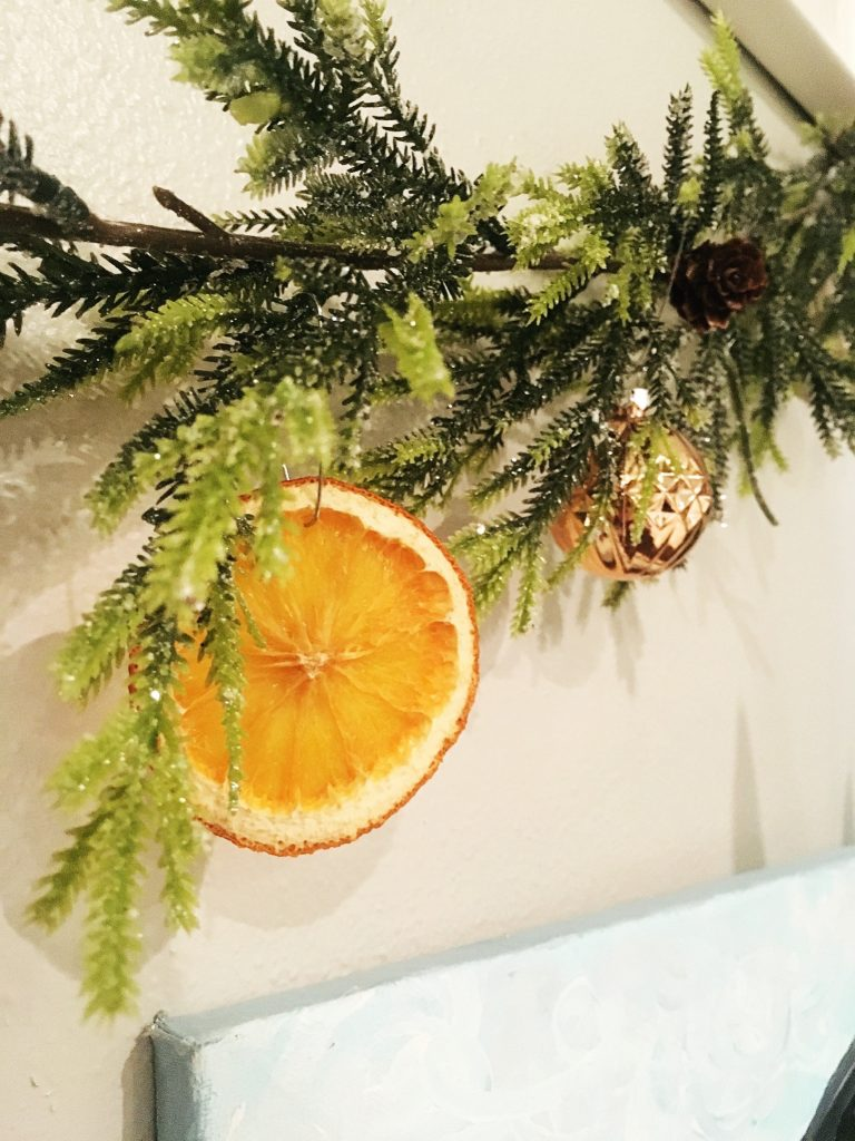 I used metal ornament hooks to hang my dried orange slices on our tree and garland.  WildflowersAndWanderlust.com