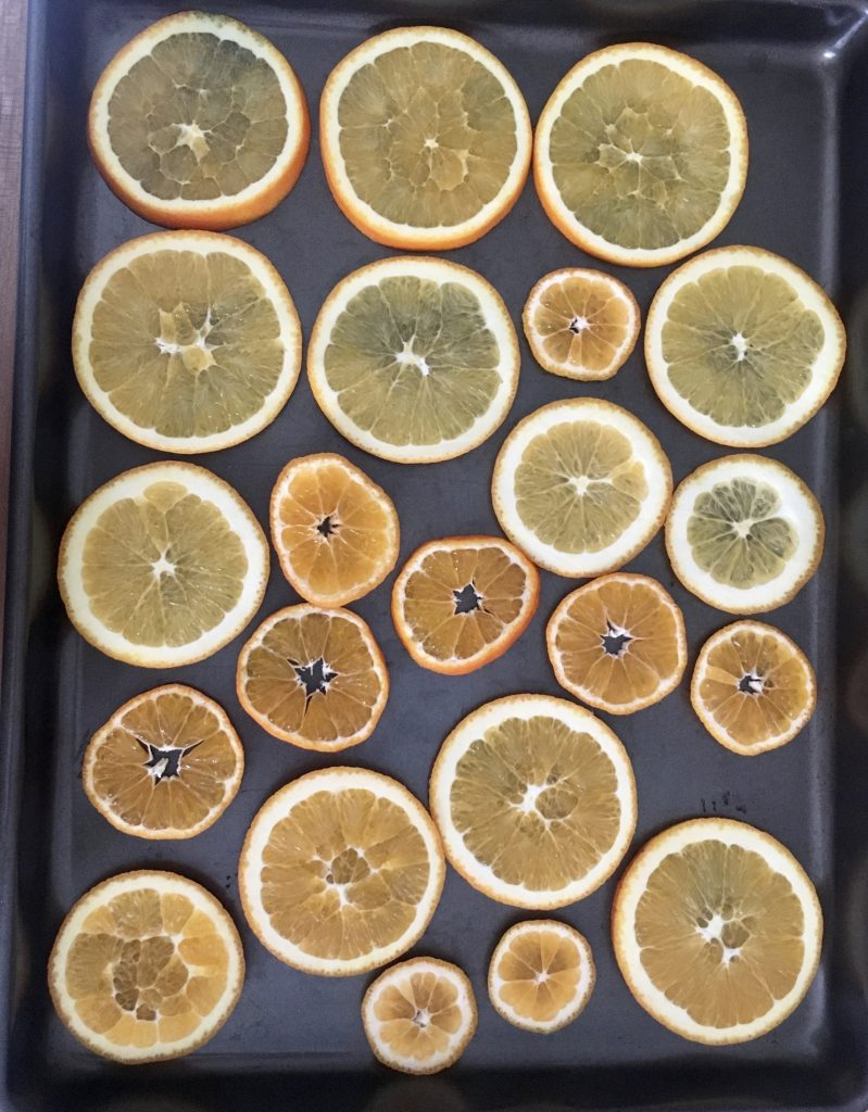 Once your oranges are sliced you're going to cook them for a few hours to dry them out  - WildflowersAndWanderlust.com