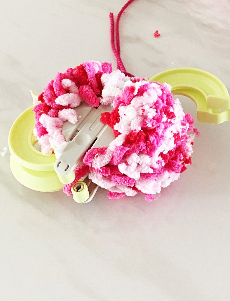 Once you have tied off the middle of your pom pom you just unfold the arms on the clover pom pom maker. WildflowersAndWanderlust.com