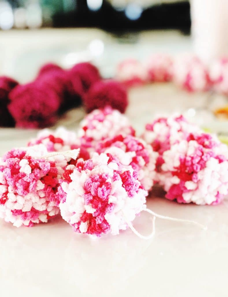 It takes anywhere from 34-40 pom poms to cover a heart shaped wire form and make a wreath. WildflowersAndWanderlust.com